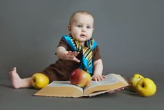 The child with the book and apples Royalty Free Stock Images