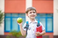 Child with book and green apple outdoors Royalty Free Stock Photos