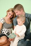 Child with book and parents royalty free stock photos