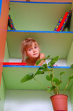 Child in the bookcase. Cute child peeking out of the bookcase stock photos