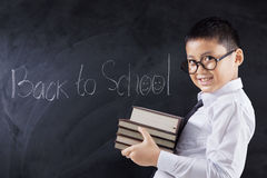 Child with books and text Back to School. Elementary school student holding books with text of Back to School on the chalkboard, shot in the class Royalty Free Stock Image