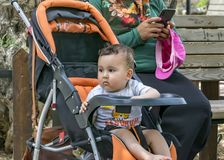A child bored sitting in a baby stroller. A female mother dressed in traditional Muslim clothing using a smartphone while walking stock photos