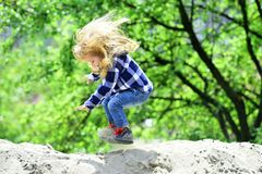 Child bounce on sand in spring or summer park. Boy jump on pile of sand on idyllic day. Kid with long blond hair in shirt, jeans outdoor. Childhood, playtime royalty free stock images