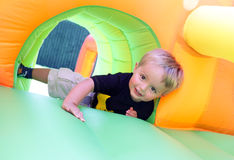 Child on bouncy castle. 2 year old boy jumping onto an inflatable bouncy castle Stock Photo