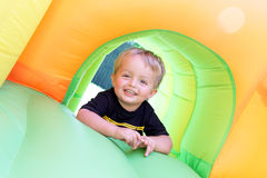 Child on bouncy castle. 2 year old boy jumping onto an inflatable bouncy castle Stock Photos