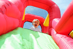 Child on bouncy castle slide royalty free stock photo