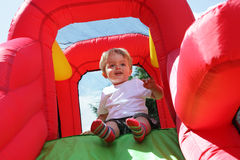 Child on bouncy castle slide Royalty Free Stock Photography