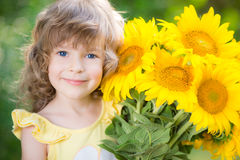 Child with bouquet of beautiful sunflowers. Happy child with bouquet of beautiful sunflowers against green background. Spring family holiday concept. Mother`s royalty free stock photos