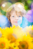 Child with bouquet of beautiful sunflowers. Happy child with bouquet of beautiful sunflowers against green background. Spring family holiday concept. Mother`s stock image