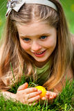 Child with bow on head find easter egg outdoor Royalty Free Stock Image