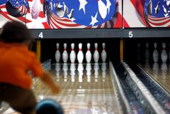 Child bowling. Young child rolling the ball at bowling alley Royalty Free Stock Image