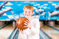 Child bowling with ball Royalty Free Stock Photos