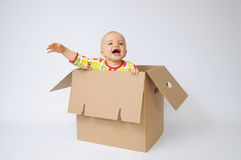 Child in the box. Beutiful child sits in the box Stock Photo