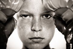 Child with boxing gloves focusing on punching pad Stock Photos
