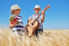 Free Child Boy And Girl With Guitar Are In The Yellow Wheat Field, Bright Sun, Summer Landscape Royalty Free Stock Images - 118856129