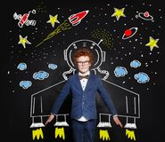 Child boy astronaut on blackboard background with space pattern.  royalty free stock image