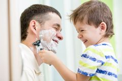Child boy attempting to shave his dad Royalty Free Stock Images