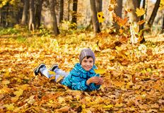 Child boy in autumn park with falling leaves. stock images