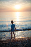Child boy on beach sunset backlight Stock Photo