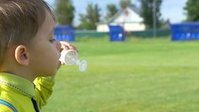 A child boy blowing soap bubbles while on a green lawn in a slow close-up motion. Happy childhood stock footage