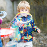 Child boy blowing soap bubbles outdoor. Three years old caucasian child boy blowing soap bubbles outdoor on birthday party - happy carefree childhood. Kid having Royalty Free Stock Photo
