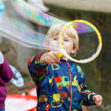 Child boy blowing soap bubbles outdoor Stock Images