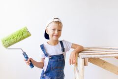 Child boy Builder makes repairs in an apartment with white walls, a worker wants to paint the walls with a roller, place for text