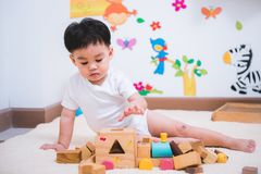 Child boy building playing toy blocks wood. Indoors room royalty free stock photo