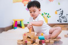 Child boy building playing toy blocks wood. Indoors room royalty free stock image