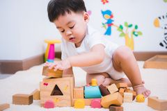 Child boy building playing toy blocks wood. Indoors room stock images