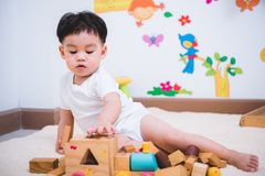 Child boy building playing toy blocks wood. Indoors room stock photo