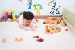 Child boy building playing toy blocks wood. Indoors room stock photography