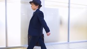 Child boy businessman walks in office corridor hurry up to work, side view. stock video footage