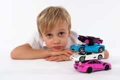 A child boy captured while playing with car toys. An adorable boy with crossed arms behind a pile of car toys stock images