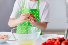 Child boy cracking egg and separating the yolk. Child helping in kitchen. Boy baking cake Royalty Free Stock Image