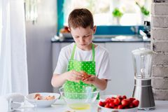 Child boy cracking egg and separating the yolk Stock Photos