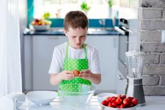 Child boy cracking egg and separating the yolk. Child helping in kitchen. Boy baking cake Royalty Free Stock Images