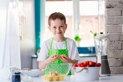 Child boy cracking egg and separating the yolk. Child helping in kitchen. Boy baking cake Royalty Free Stock Photo