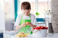 Child boy cracking egg and separating the yolk. Child helping in kitchen. Boy baking cake Stock Photography