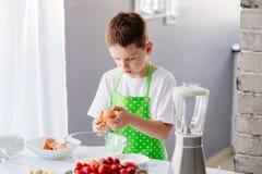 Child boy cracking egg and separating the yolk Royalty Free Stock Image