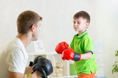 Child boy and dad play boxing. Child boy and his dad play boxing in nursery royalty free stock photography