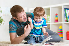 Child boy and dad read a book on floor at home Royalty Free Stock Photography