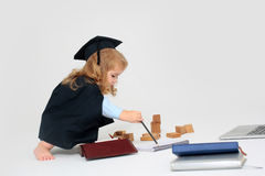 Child boy drawing by pencil. Little boy child in graduation squared cap and black mantle sitting and drawing by pencil in copy book near box with colored pencils Stock Photos