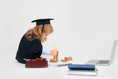 Child boy drawing by pencil. Little boy child in graduation squared cap and black mantle sitting and drawing by pencil in copy book near box with colored pencils Stock Images