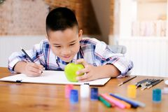 Child boy drawing picture at home. stock photo