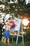 Child Boy Drawing Picture Outdoors in Summer park. At sunset stock photography