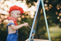 Child Boy Drawing Picture Outdoors in Summer park. At sunset royalty free stock image