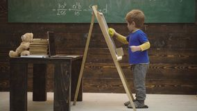 Child boy draws on chalkboard. Little schoolboy wiping chalkboard. Back to school message against boy writing with chalk stock footage