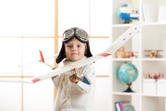 Child boy dressed like a pilot with toy airplane playing at home Stock Image