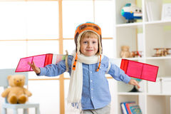 Child boy dressed like a pilot with toy wings playing at home Royalty Free Stock Photos